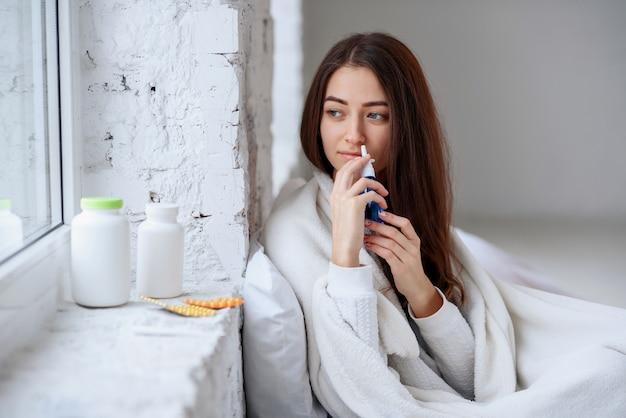 Belle femme à l'aide d'un vaporisateur nasal