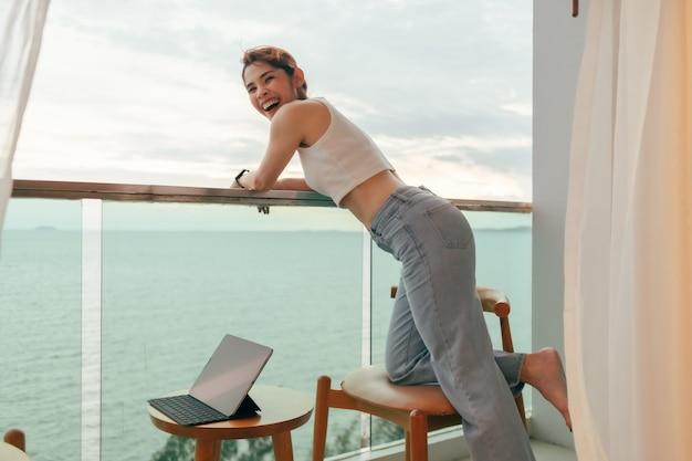 Belle femme aime regarder la vue sur la mer depuis le balcon de l'hôtel