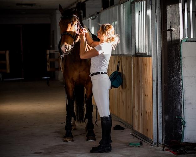 Belle femme ajuste la bride de son cheval dans l'écurie en été dans les rayons du coucher du soleil.