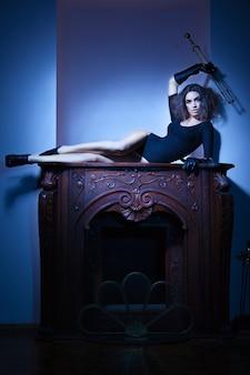 Belle femme allongée sur la cheminée dans la vieille maison