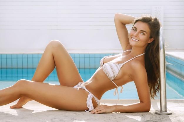 Belle femme allongée à côté d'une piscine