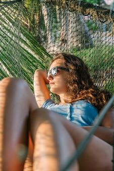 Belle femme allongée dans un hamac près de l'océan.