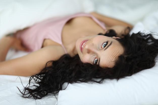 Belle femme allongée dans son lit sous un manteau et regarde sous le front.