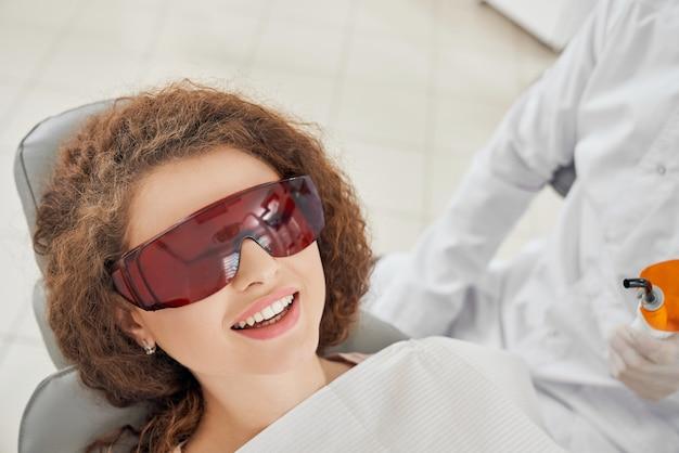 Belle femme allongée sur un fauteuil dentaire dans des lunettes de protection