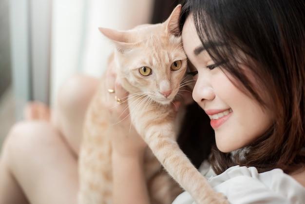 Belle femme amateur de chat asiatique joue avec le chat dans sa chambre
