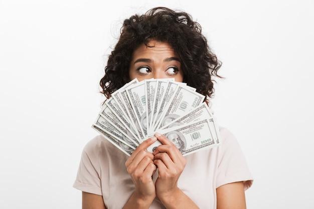 Belle femme américaine avec une coiffure afro couvrant le visage avec un ventilateur d'argent en dollars et en regardant de côté, isolé sur un mur blanc
