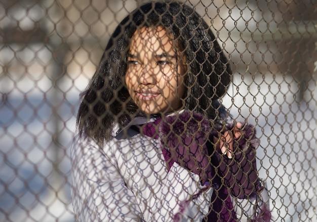 Belle femme américaine souriante dans la rue à l'extérieur derrière le réseau