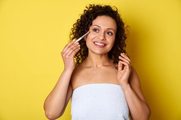 Belle femme appliquant des cosmétiques avec un pinceau de maquillage sur fond jaune