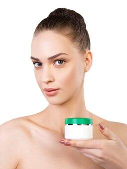 Belle femme appliquant une crème cosmétique. portrait de femme isolée. traitement de beauté