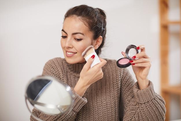 Belle femme appliquant le maquillage