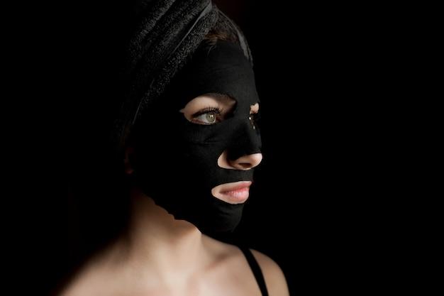Belle femme appliquant un masque facial noir. soins de beauté. close-up portrait of spa girl appliquer le masque facial à l'argile sur fond noir