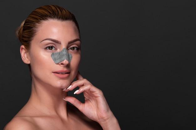 Belle femme appliquant un produit de soin de la peau