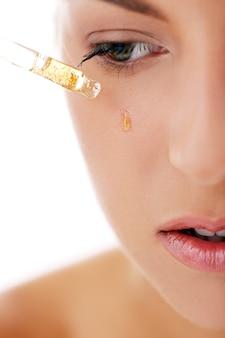 Belle femme appliquant des produits cosmétiques