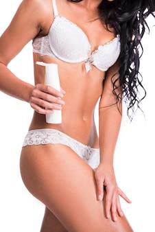 Belle femme applique une crème pour le corps sur ses jambes.