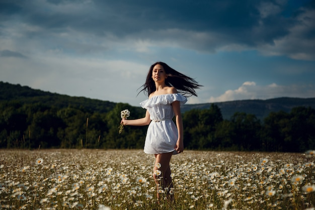 Belle femme appréciant le champ, jolie fille aux cheveux noirs se détendre en plein air, s'amuser, tenant la plante, heureuse jeune femme et la nature verte du printemps, concept d'harmonie