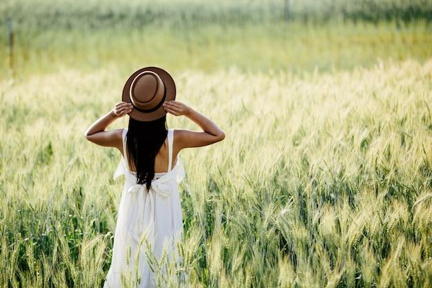 Belle femme appréciant dans les champs d'orge.