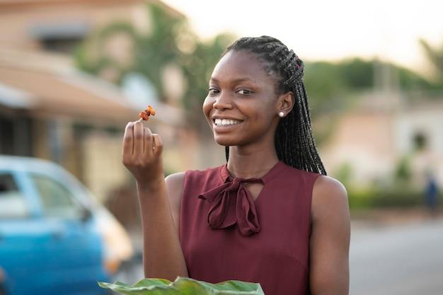 Belle femme appréciant de la nourriture de rue