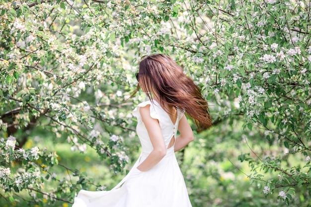 Belle femme appréciant l'odeur dans le jardin de cerisier de printemps