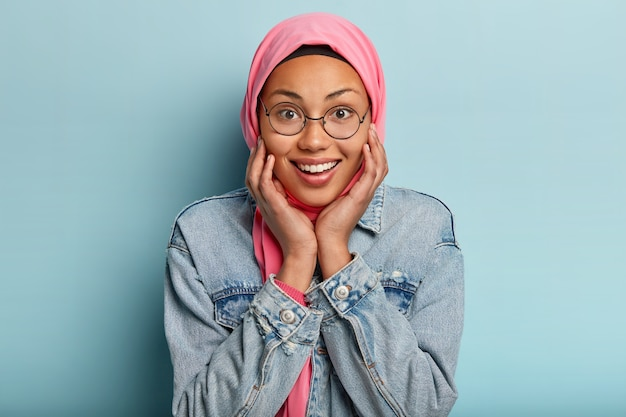 Belle femme arabe heureuse touche doucement les joues, a un sourire charmant, porte un voile rose traditionnel sur la tête