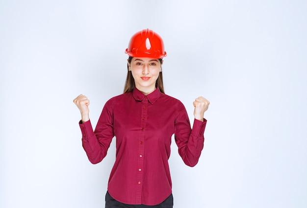 Belle femme architecte en casque dur rouge regardant la caméra sur un mur blanc.