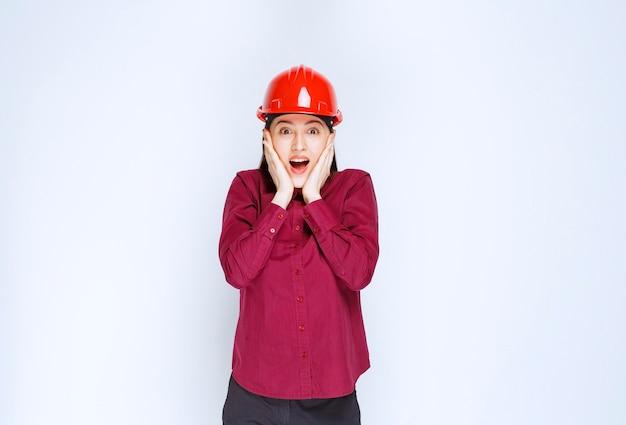 Belle femme architecte en casque dur rouge surpris de quelque chose.