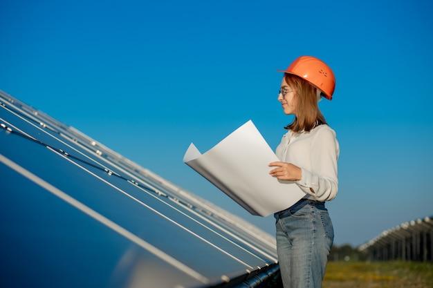 Belle femme architecte examinant un projet de carte ou un plan de projet, l'activité des travailleurs à la recherche dans la ferme de cellules photovoltaïques ou sur le terrain de panneaux solaires.