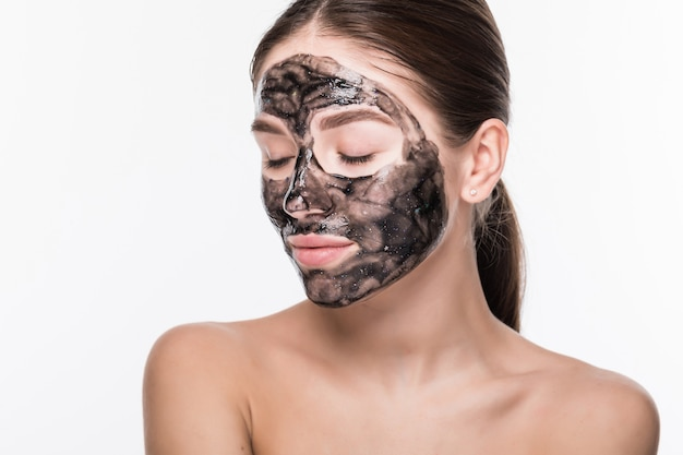 Belle femme avec de l'argile ou un masque de boue sur son visage isolé sur mur blanc