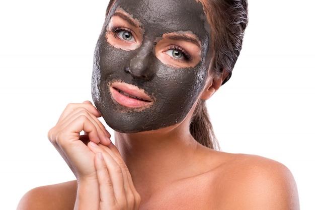 Belle femme avec de l'argile ou un masque de boue sur son visage