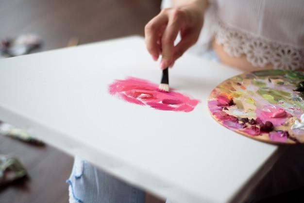 Belle femme artiste dessinant sa photo sur toile avec des couleurs à l'huile à la maison