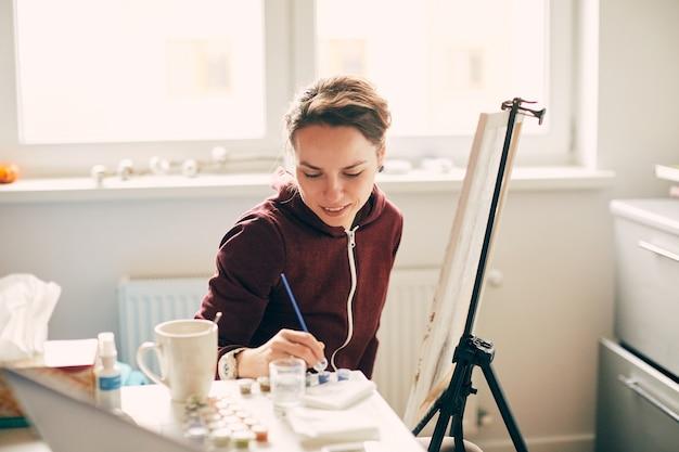 Belle femme artiste peinture à la maison sur toile blanche, passe-temps femme à l'intérieur de l'appartement propre