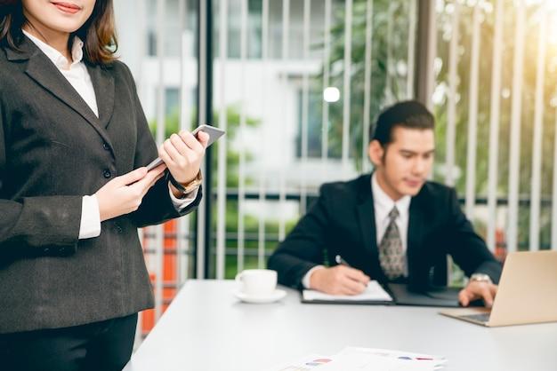 Belle femme asiatique d'affaires en costume tenant la tablette dans les mains pendant que son patron travaille sérieusement