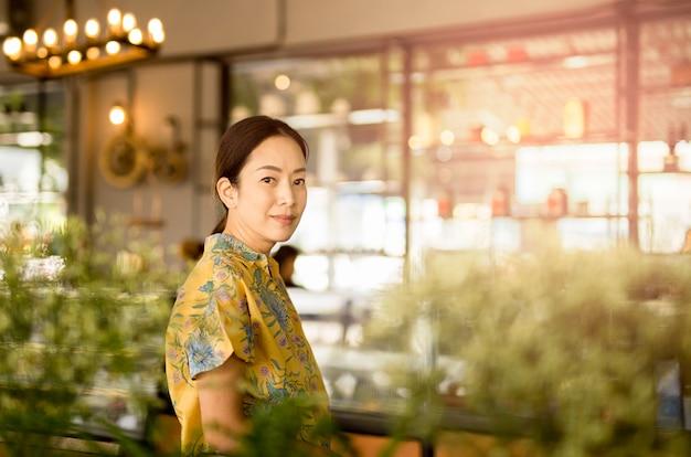 Belle femme asiatique âgée moyenne en regardant la caméra dans le café-restaurant.