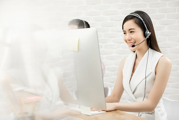 Belle femme asiatique agent de service client télémarketing travaillant dans le centre d'appels