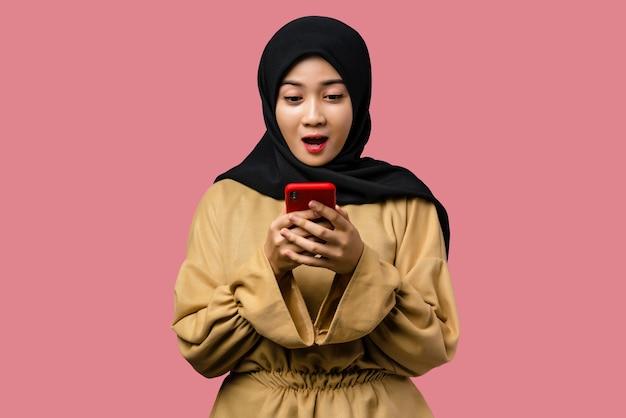 Belle femme asiatique à l'aide d'un smartphone avec une expression surprise