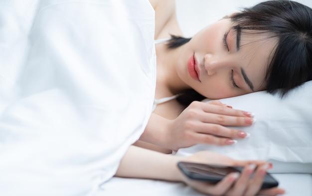 Belle femme asiatique à l'aide de téléphone sur le lit dans la chambre