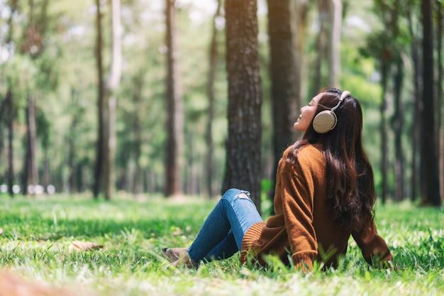 Une belle femme asiatique aime écouter de la musique avec un casque avec un sentiment de bonheur et de détente dans le parc