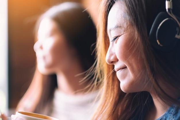 Une belle femme asiatique aime écouter de la musique avec un casque tout en buvant du café avec des amis