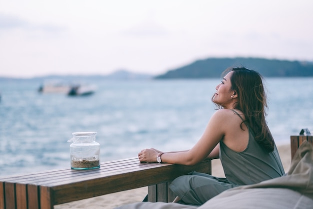 Une belle femme asiatique aime s'asseoir sur la plage au bord de la mer