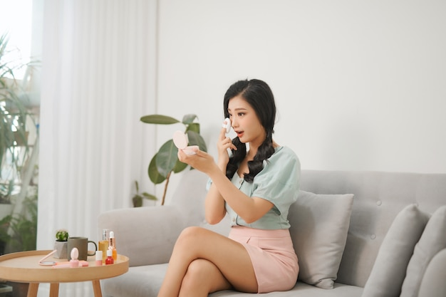Belle femme asiatique appliquant et maquillage sur son visage avec bouffée