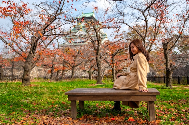 Une belle femme asiatique apprécié assis sur une branche en bois dans le jardin d'automne
