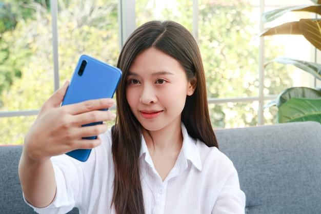 Belle femme asiatique asseyez-vous et détendez-vous sur le canapé du salon de la maison. elle tient un smartphone pour se prendre en photo. profitez d'être seul. concept d'utilisation d'outils de communication modernes
