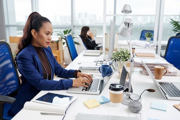 Belle femme asiatique assis au bureau dans un bureau occupé et travaillant sur un ordinateur portable