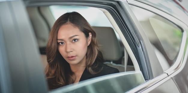 Belle femme asiatique assise sur la banquette arrière de la voiture moderne tout en regardant