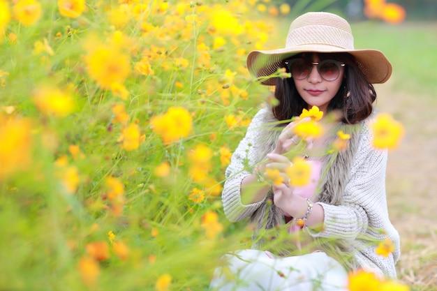 Belle femme asiatique assise dans la nature parmi les champs de fleurs cosmos avec pacifique
