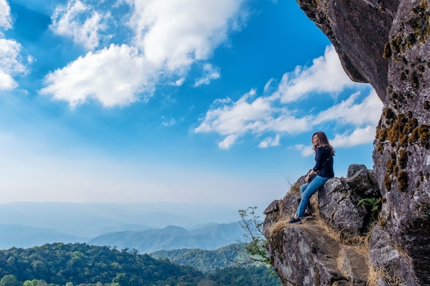 Une belle femme asiatique assise sur une falaise avec vue sur les montagnes et fond de ciel bleu