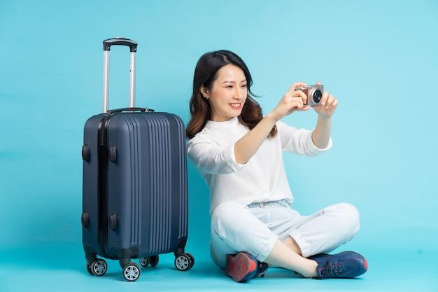 Belle femme asiatique assise posant à côté de la valise et se préparant à voyager