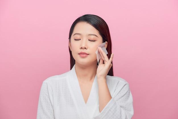 Belle femme asiatique attirante utilisant le film propre d'huile faciale pour enlever l'huile sur le visage