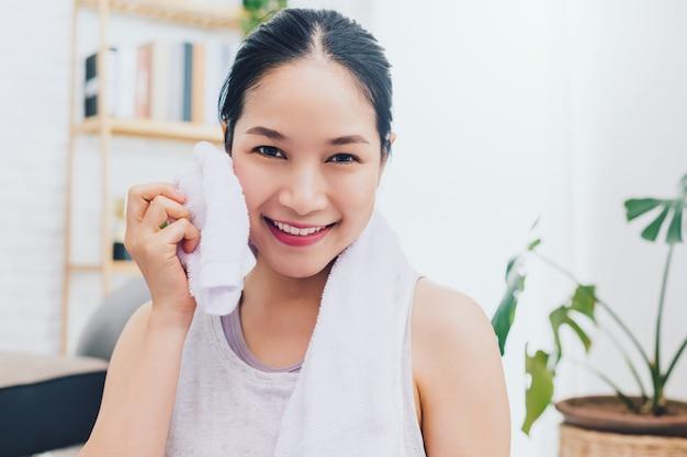 Belle femme asiatique au repos et tenant une serviette après avoir joué au yoga et faire de l'exercice à la maison