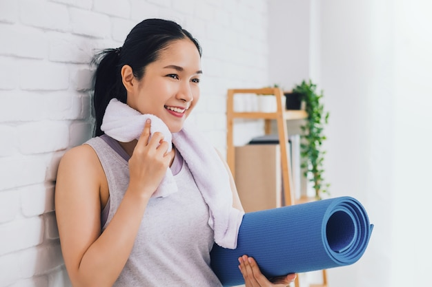 Belle femme asiatique au repos et tenant un tapis de yoga après avoir joué au yoga