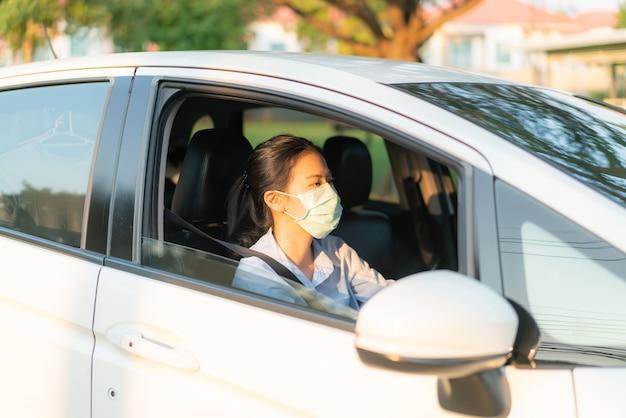 Belle femme asiatique au volant d'une voiture portant un masque pour aller à l'extérieur rester en bonne santé pour se protéger contre le coronavirus covid-19 infection par le virus épidémie de maladie pandémie mondiale, émission de pollution atmosphérique